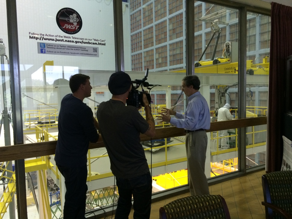 Filming in front of the large observation window by the High Bay Clean Room where the James Webb Space Telescope is being assembled